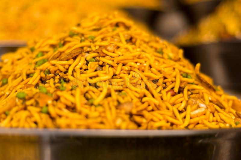 Closeup of namkeen in steel plate. Yellow colored namkeen in steel plate kept at a shop in the daylight. Namkeen is a salty Indian snack royalty free stock image
