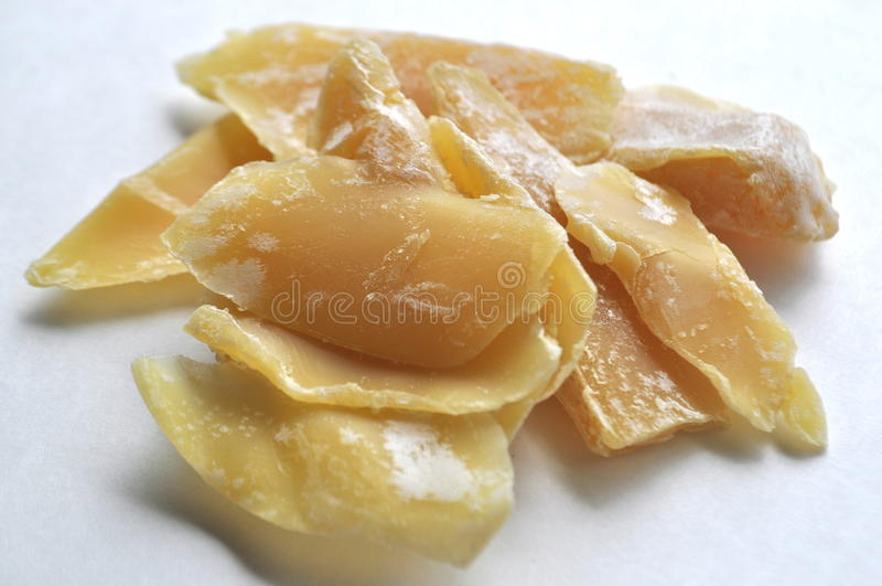 A closeup of a natural beeswax shavings for cosmetic use and candlemaking on white royalty free stock image