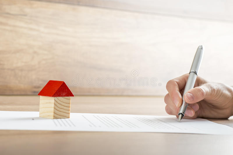 Closeup of new homeowner signing a contract of house sale or mor. Tgage papers with a wooden toy house on the document. Suitable for real estate concept stock photos