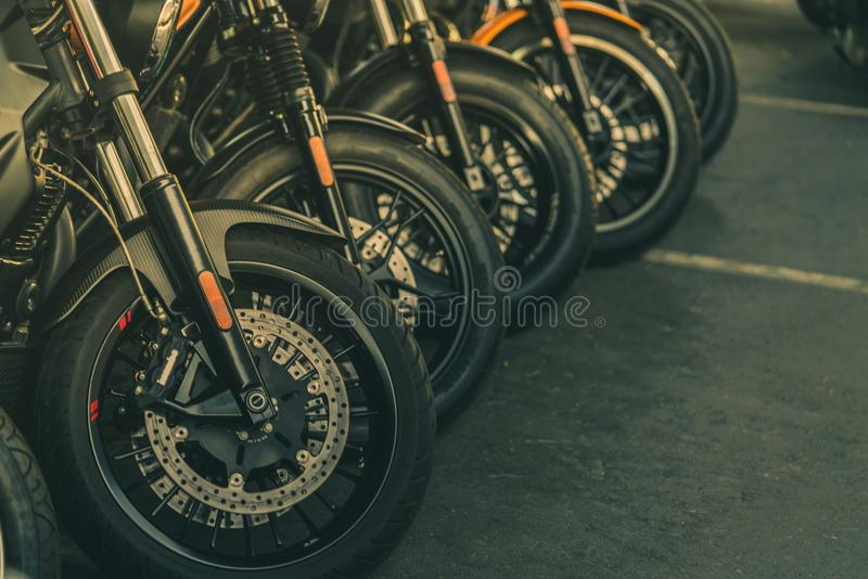 Closeup of new motorbike front wheel . Big bike parked on asphalt road. Iconic motorcycle with sports design. Black tire royalty free stock image