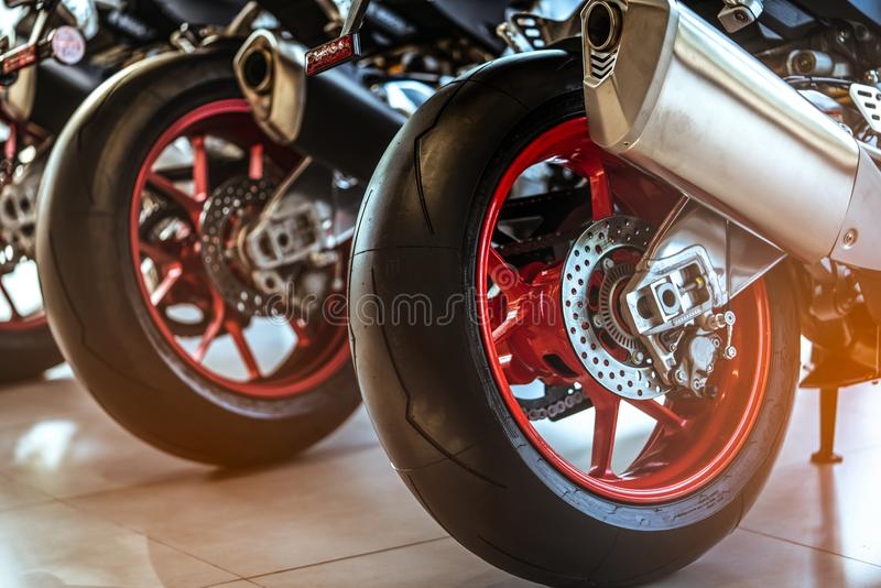 Closeup of new motorbike rear wheel . Big bike parked in showroom of dealership. Motorcycle exhaust pipes. Iconic motorcycle stock photography