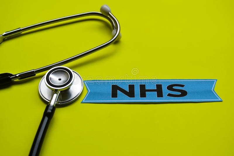 Closeup NHS with stethoscope concept inspiration on yellow background royalty free stock image