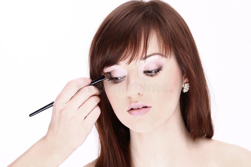 closeup O artista de composição aplica a sombra de olho Face bonita da mulher imagens de stock royalty free