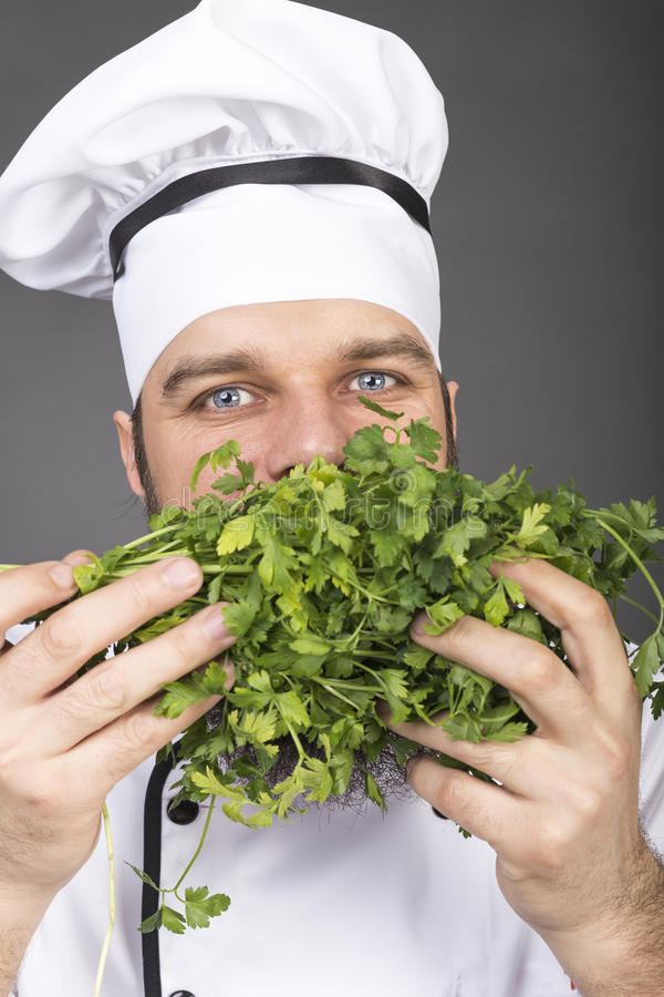 Free Closeup Of Happy Young Chef Smelling Parsley Royalty Free Stock Photo - 71524175