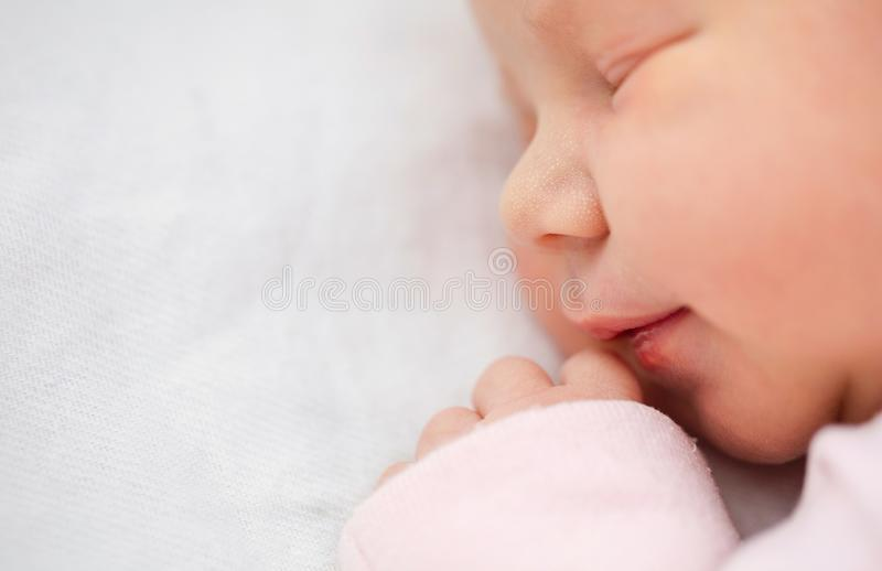 Closeup ofe beautiful one day old girl smiling in her sleep stock image