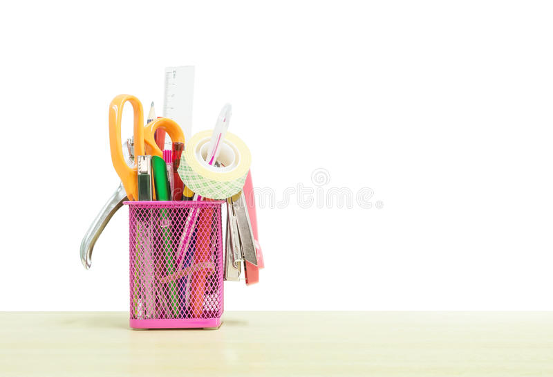Closeup office equipment with pink steel box for pen on blurred wooden desk in the meeting room under window light isolated on. Office equipment with pink steel stock photography