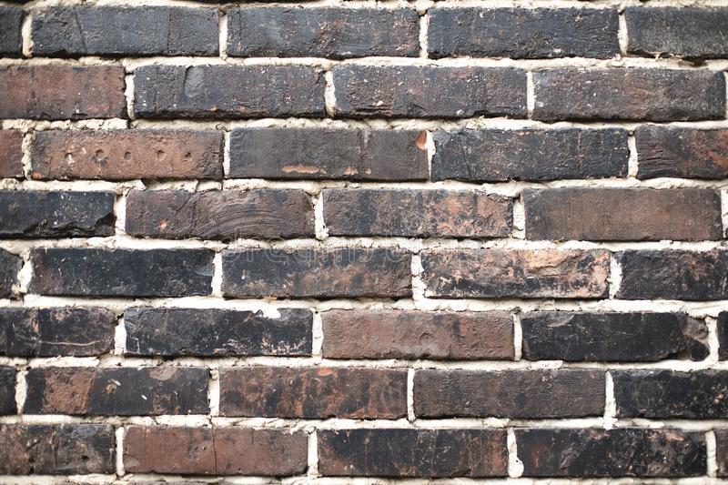 Closeup of old brown dark brick wall. With white seams. For pattern, texture and background grey textured construction block building backdrop cement space royalty free stock image