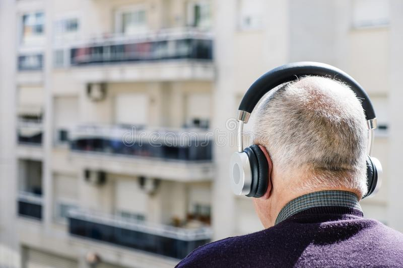 Old caucasian man using headphones stock image