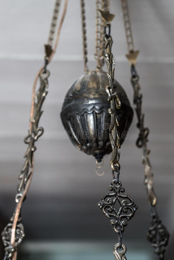 Detail of an old, patinated antique brass lamp with cast filigran decoration. Closeup of old-fashioned decorative lighting hanging from the ceiling in royalty free stock photo