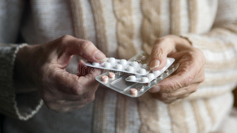 Closeup of old female hands holding pills royalty free stock image