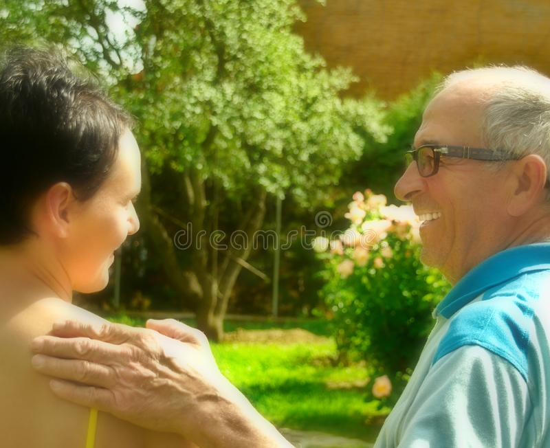 Old man smiling and cheering a young woman up stock photography