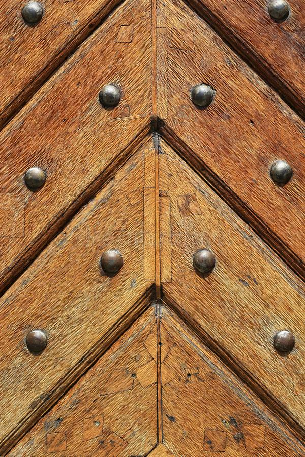 Closeup of old vintage wooden doors with metal rivets. Fragment of old vintage wooden doors with metal rivets, close-up architectural texture stock photography