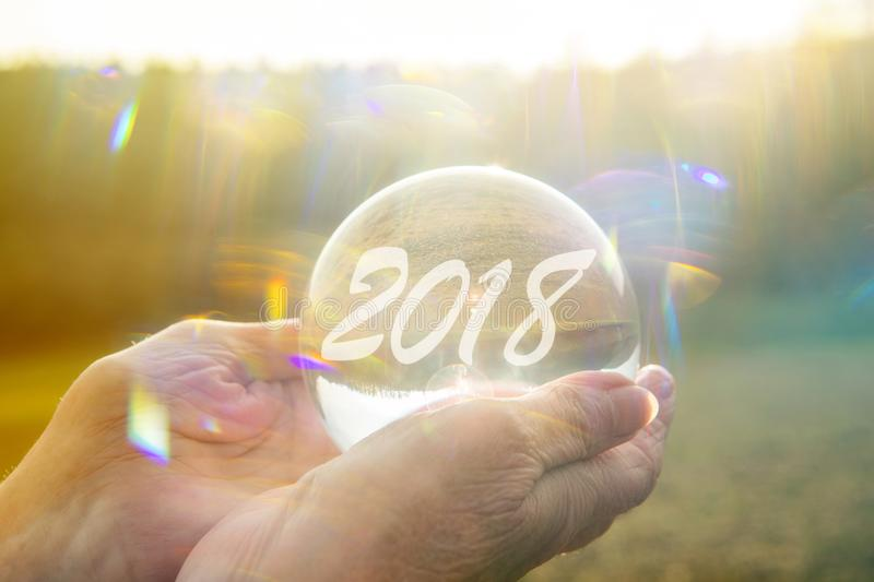 Older woman holding glass sphere with 2018 royalty free stock images