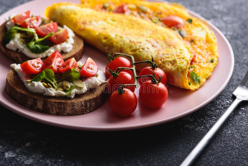 Closeup Omelette with cherry tomatoes, sandwiches witn riccota and pesto. Frittata - italian omelet royalty free stock images