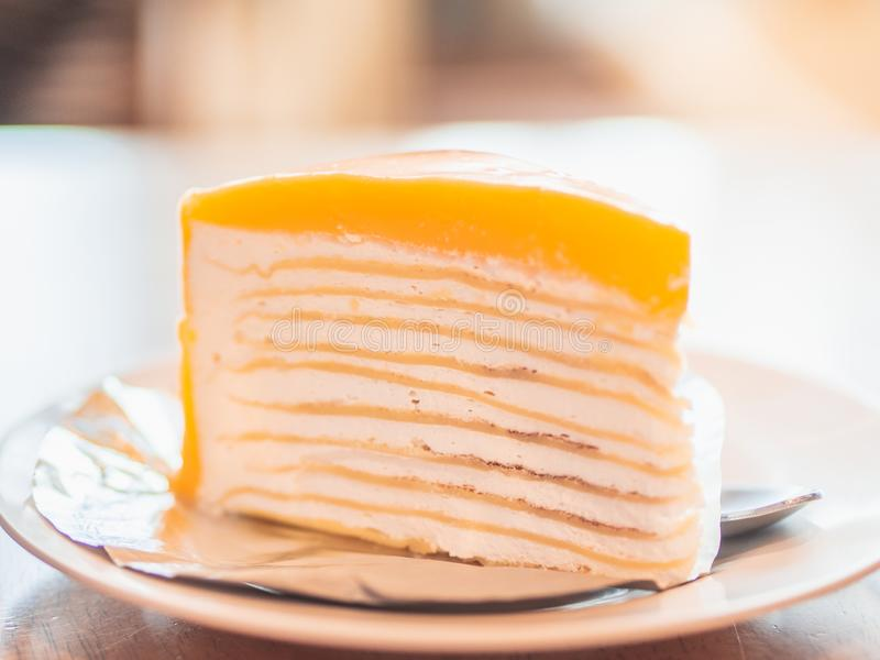 Closeup Orange Crepe Cake on white plate in cafeteria. stock photos