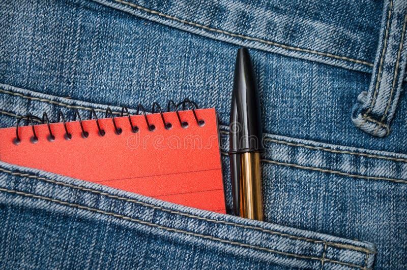 Orange notebook and black pen in blue jeans pocket stock image