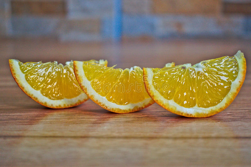 Orange Wedges. Closeup of orange wedges on a wooden table royalty free stock photos