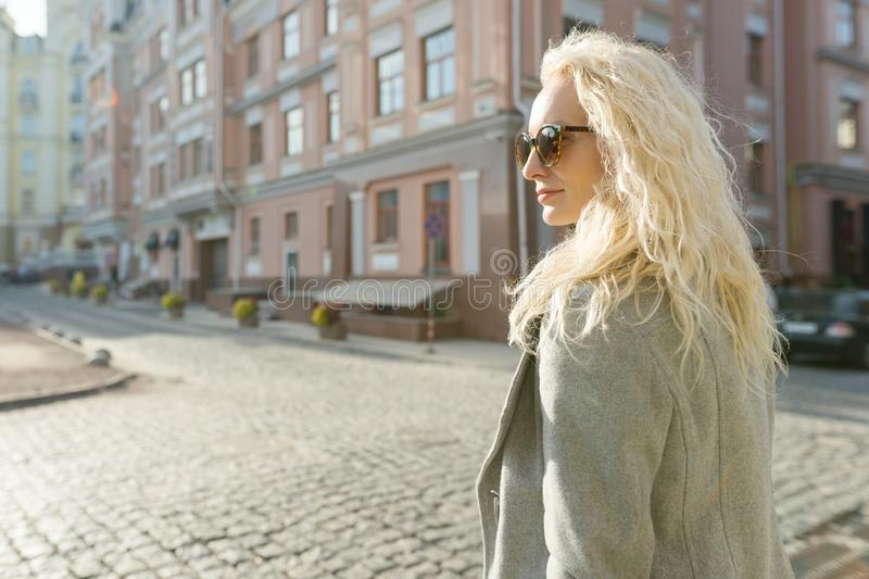 Closeup outdoor portrait of a young smiling blond woman with sunglasses with long curly hair. On city street sunny day, golden hou stock photos