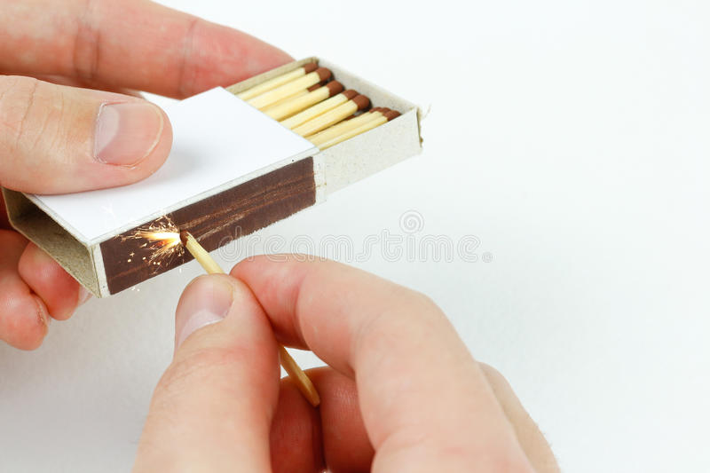 Closeup outdoor white boxes of matches. Hands strike a match royalty free stock photos