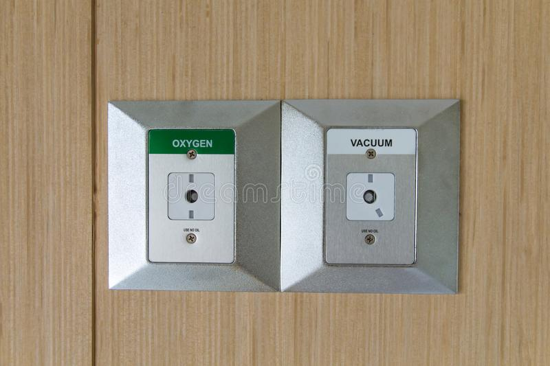 Closeup oxygen and vacuum plug sockets on the wall in a hospital patient room,Medical hospital oxygen inhalation device. Health, air, equipment, emergency stock photography