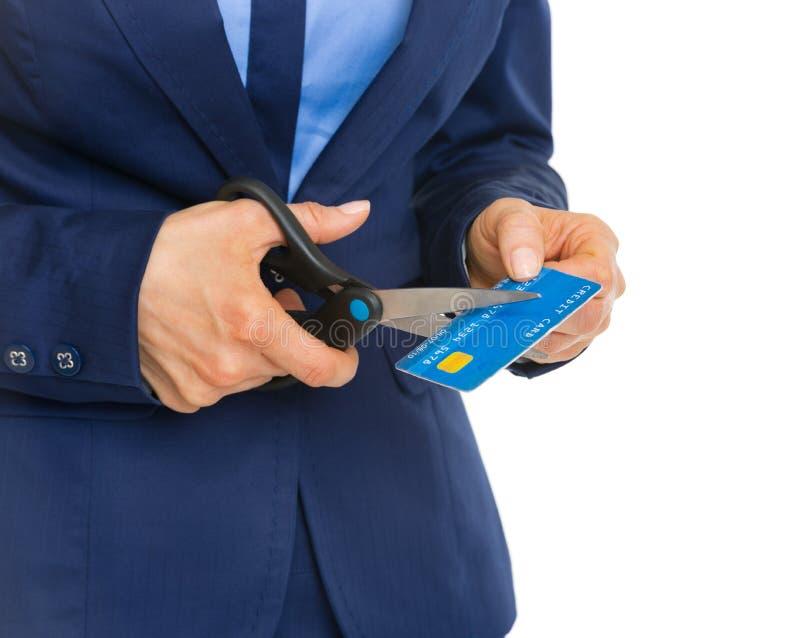 Closeup på bitande kreditkort för affärskvinna med sax arkivfoto