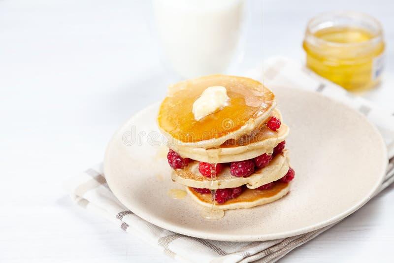 Closeup på bunt av ny hemlagad pannkakabunt med hallonet, smältande smör och hällande honung eller marplesirap amerikansk arkivfoton
