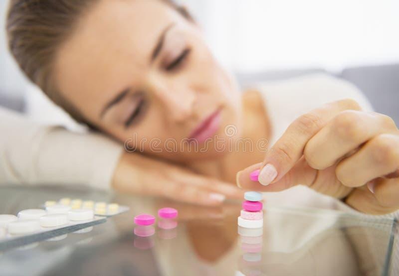 Closeup på den frustrerade unga kvinnan som spelar med preventivpillerar fotografering för bildbyråer