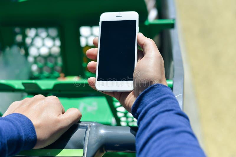 Closeup på den hållande mobila smartphonen för person i hand under shopping arkivfoton