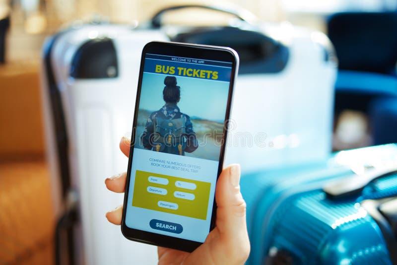 Closeup på den kvinnliga handen med telefonen som bokar biljetter genom att använda appen arkivfoto