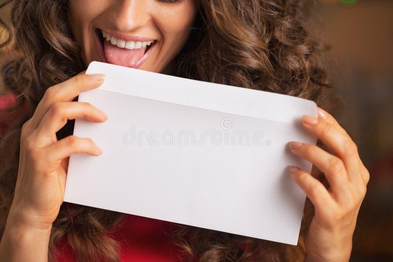 Closeup på den lyckliga unga kvinnan som slickar kuvertet royaltyfri fotografi