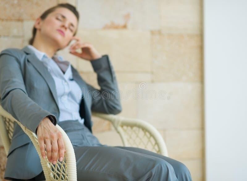 Closeup på den trött affärskvinnan som kopplar av på stol royaltyfri fotografi