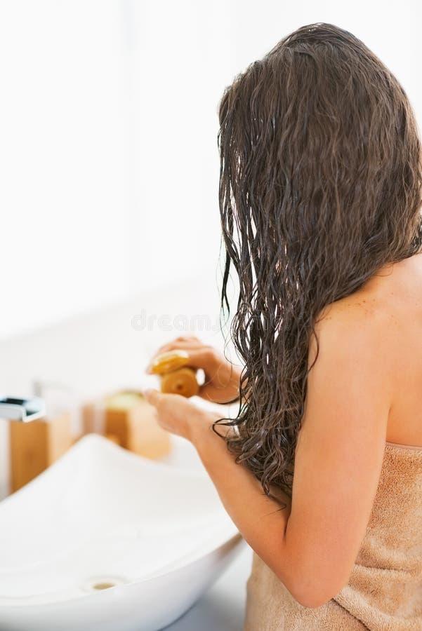 Closeup på den unga kvinnan som applicerar hårmaskeringen arkivbilder