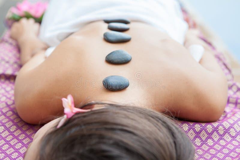 Closeup på den unga kvinnan som har varm stenmassage på baksida i brunnsort royaltyfri foto