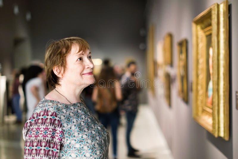 Closeup på den uppmärksamma höga kvinnan som besöker museet och tycker om a royaltyfri fotografi