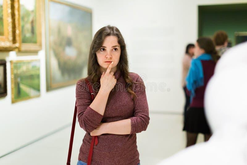 Closeup på den uppmärksamma kvinnan som besöker museet och tycker om sculture royaltyfri foto