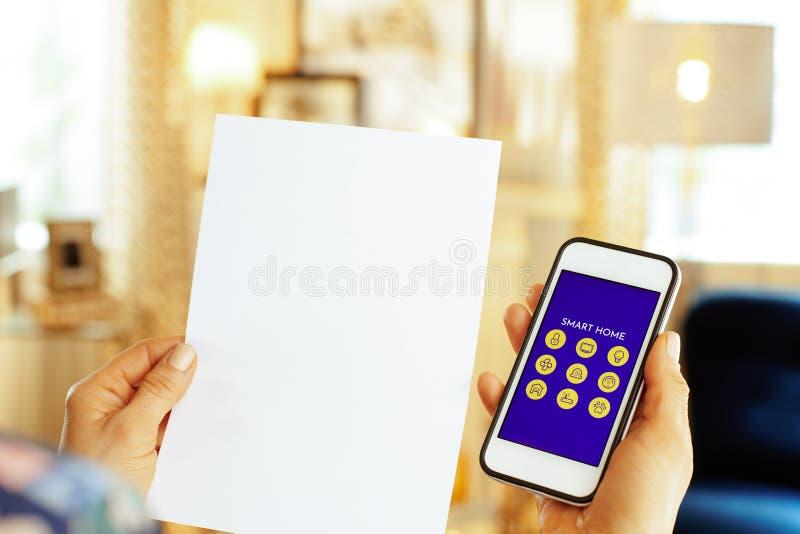 Closeup på det tomma pappers- arket och smartphonen med den smarta hem- appen royaltyfri fotografi