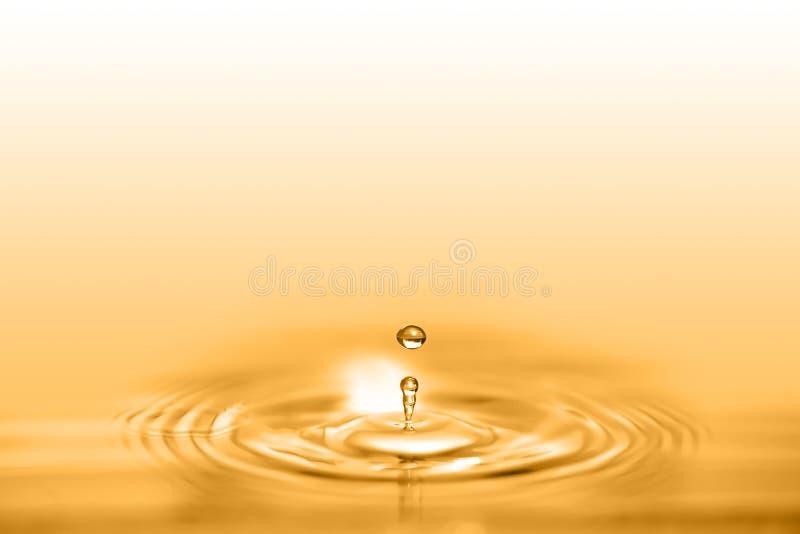 Closeup på droppe av kosmetisk flytande för guld- olja som skapar en circula royaltyfri foto