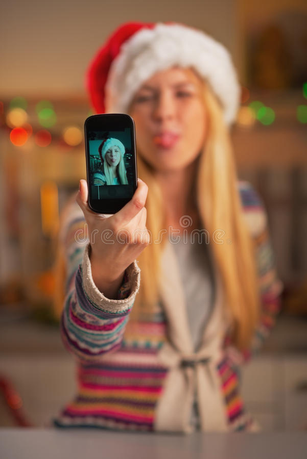 Closeup på gladlynt tonårs- flicka i den santa hatten som tar självfotoet royaltyfri bild