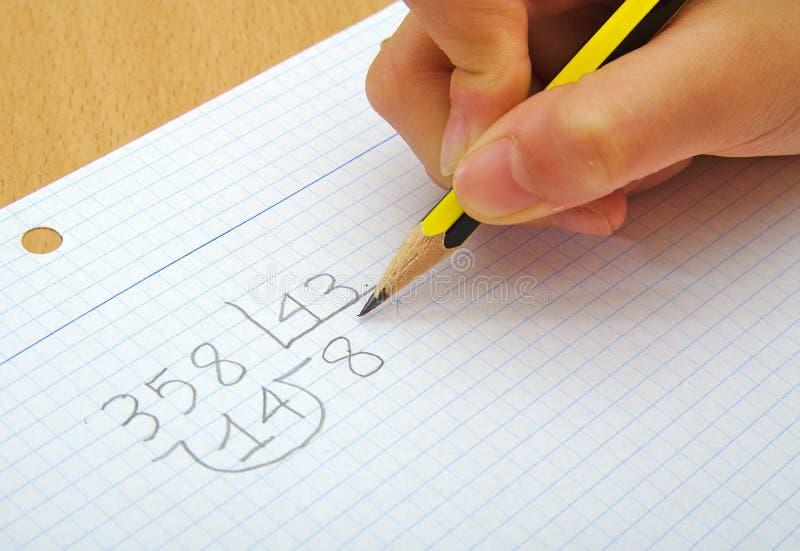 Closeup på händerna av ett barn som gör matematik arkivfoton
