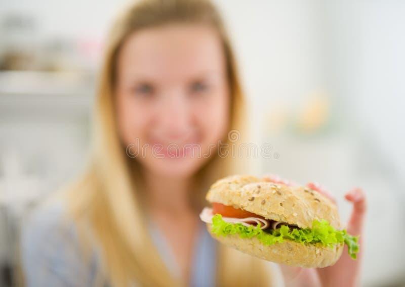 Closeup på hamburgaren i hand av tonåringflickan arkivfoto
