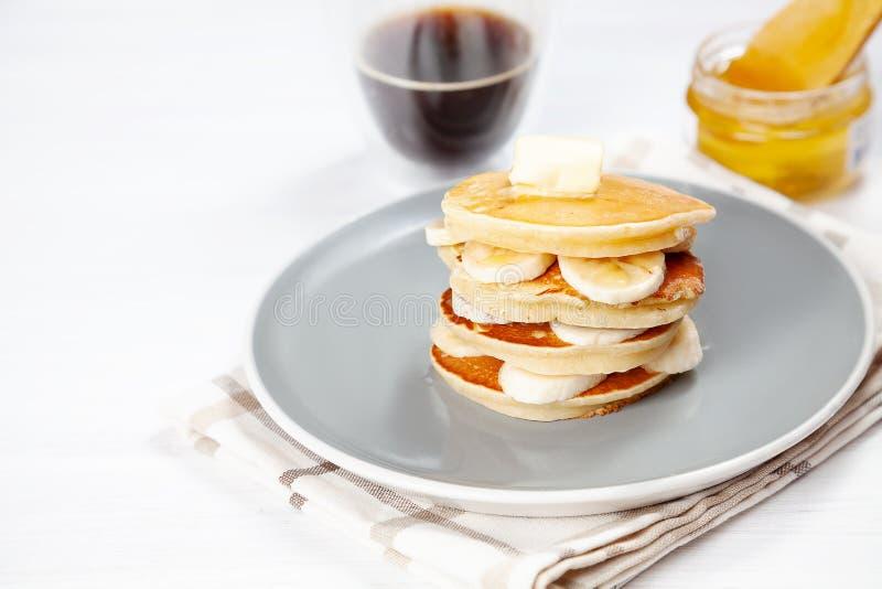 Closeup på ny hemlagad pannkakabunt med bananen, smältande smör och hällande honung eller marplesirap amerikansk pannkaka med royaltyfria bilder