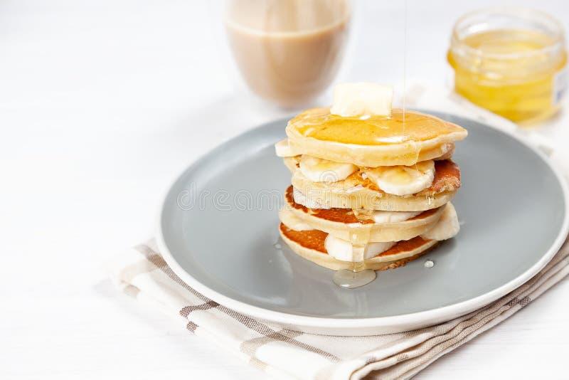 Closeup på ny hemlagad pannkakabunt med bananen, smältande smör och hällande honung eller marplesirap amerikansk pannkaka med arkivfoton