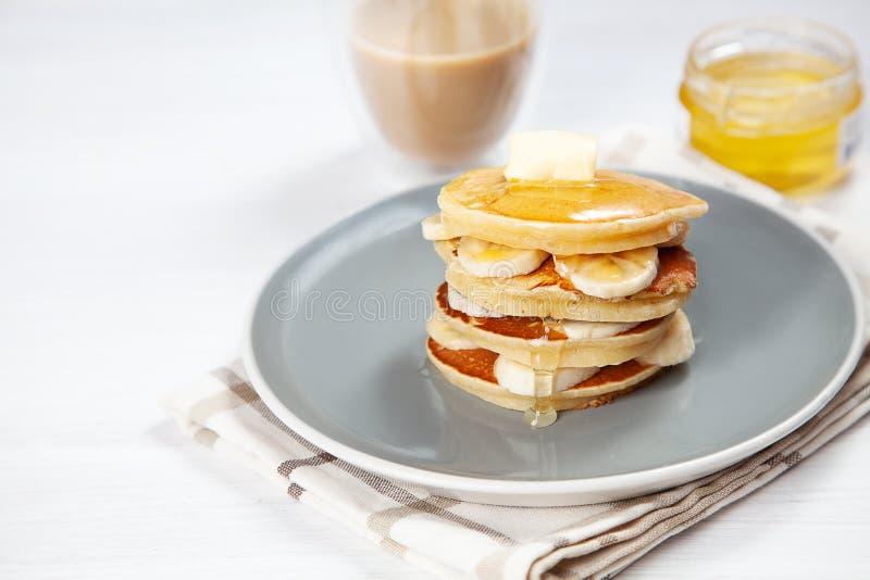 Closeup på ny hemlagad pannkakabunt med bananen, smältande smör och hällande honung eller marplesirap amerikansk pannkaka med royaltyfria foton