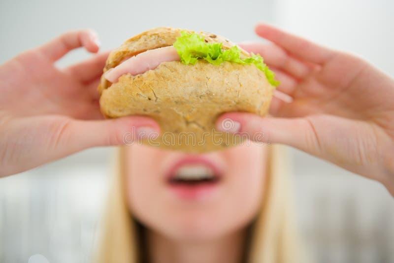 Closeup på tonåringflickan som äter hamburgaren arkivfoton