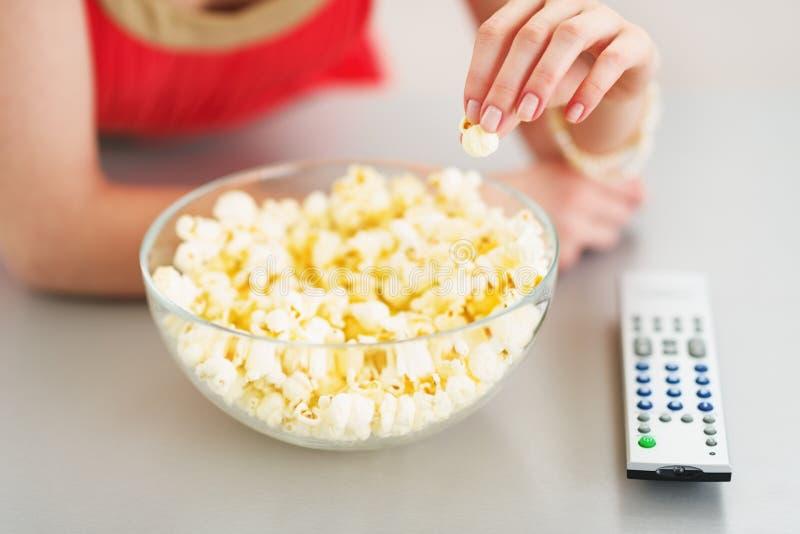 Closeup på tonåringflickan som äter popcorn och håller ögonen på tv royaltyfria bilder