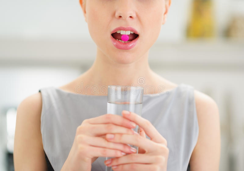 Closeup på ung kvinna med preventivpilleren i mun arkivbilder