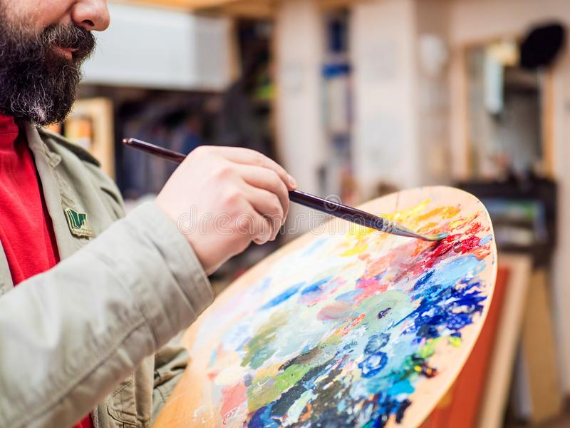 Closeup of painter artist mix the paints and working in a modern abstract oil canvas in his studio. stock image