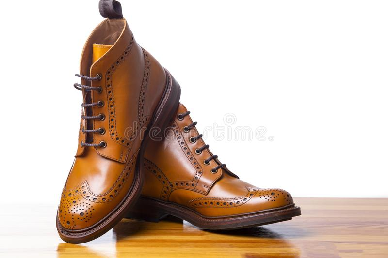 Closeup of Pair of High Men`s Tanned Brogues Boots. Footwear Concepts.Closeup of Pair of High Men`s Tanned Brogues Boots. Isolated Over White Background royalty free stock image