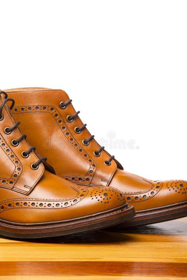 Closeup of Pair of High Mens Tanned Brogues. Footwear Concepts.Closeup of Pair of High Men`s Tanned Brogues Boots. Isolated Over White Background.Vertical Image stock photos