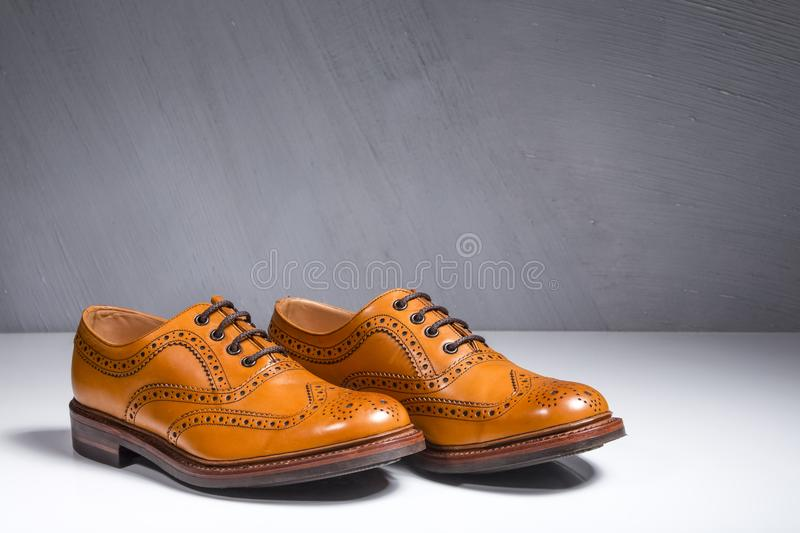 Closeup of Pair of Luxury Male Full Broggued Tan Leather Oxfords. Shoes On White Surface. Against Gray Wall. Horizontal Shot stock image